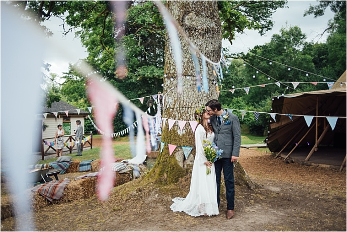 Colourful, creative festival wedding in Devon. Cool yurt village venue, bunting and haybales. Photos by Liberty Pearl Photography