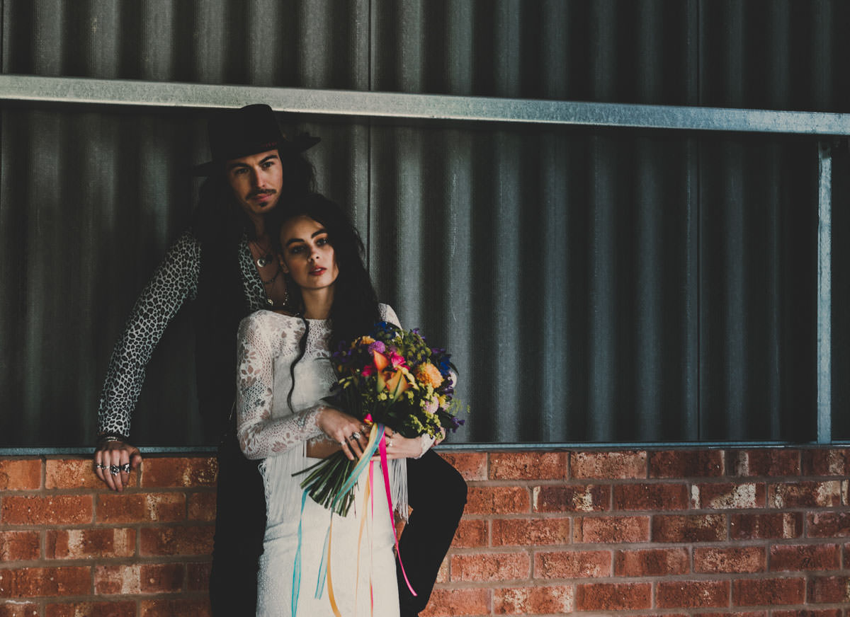 alternative barn wedding, alternative weddings, barn wedding, bright confetti, colourful wedding flowers, colourpop wedding colourful wedding, edgy bride, exclusive venue hire, fedora hats, festival bride, festival wedding, fringing, glitter face makeup, Jade Maguire photography, Ophelia rose, painted leather jacket, pom poms, Skikoba bride, statement wedding flowers, the giraffe shed, wales wedding, wales wedding venues, wedding glitter, wedding leather jackets