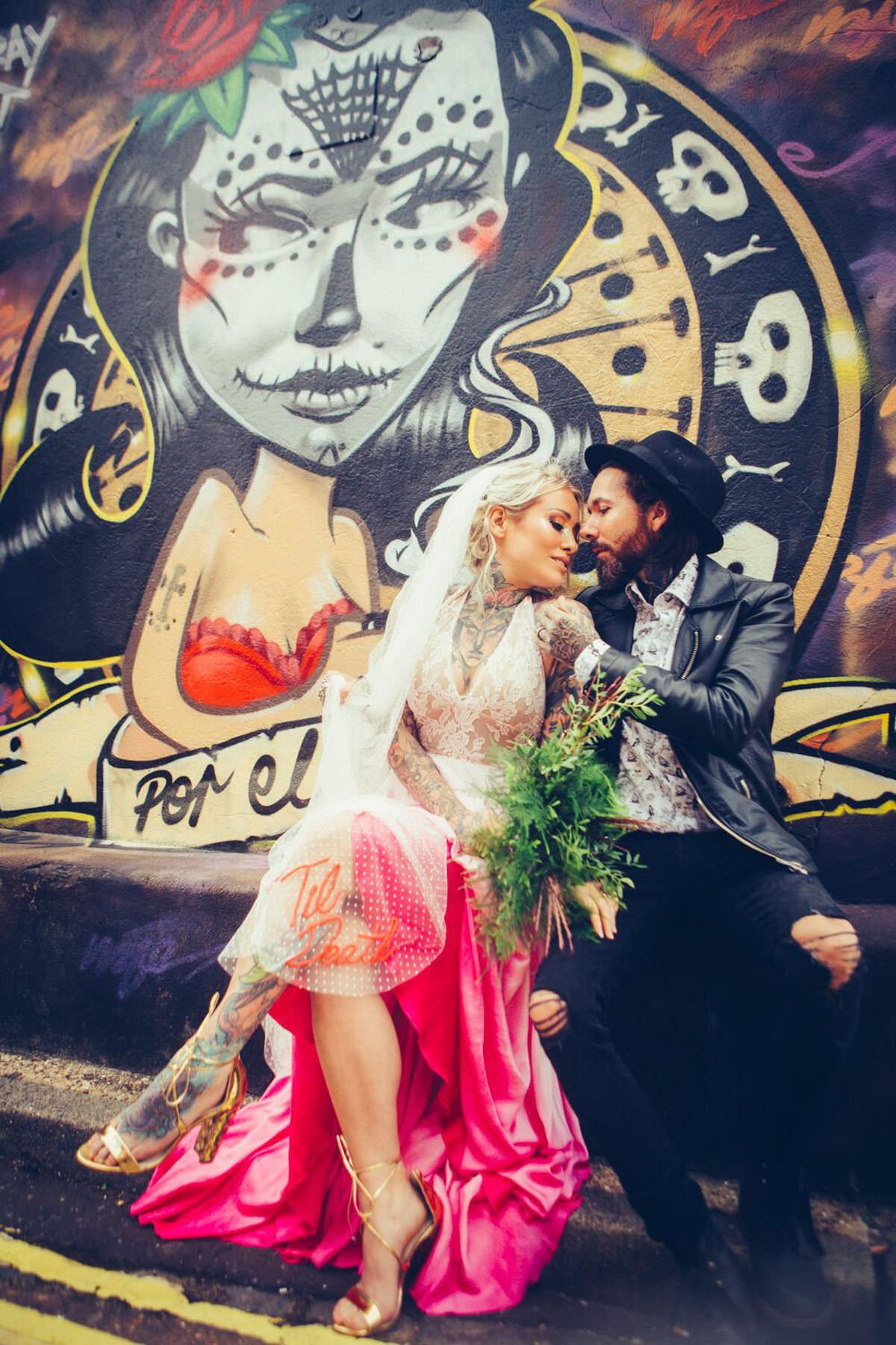 edgy tattoo bride wearing pink wedding dress