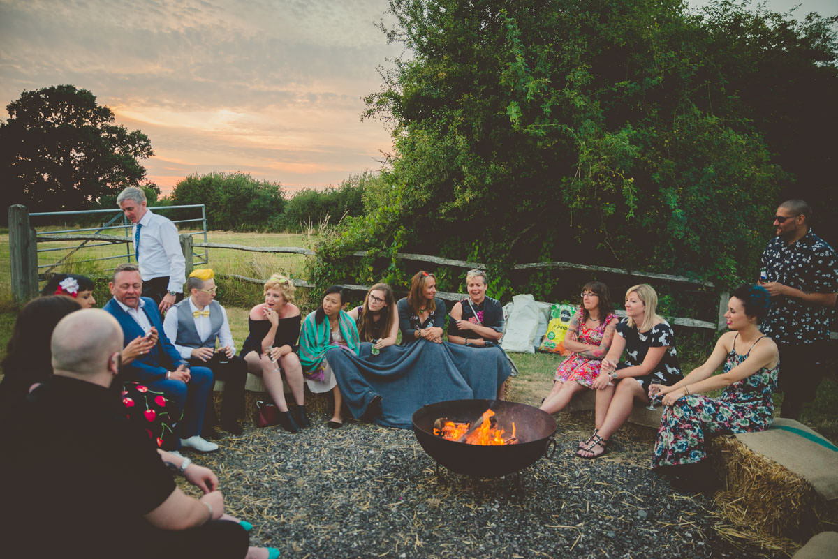 wedding guests around fire pit