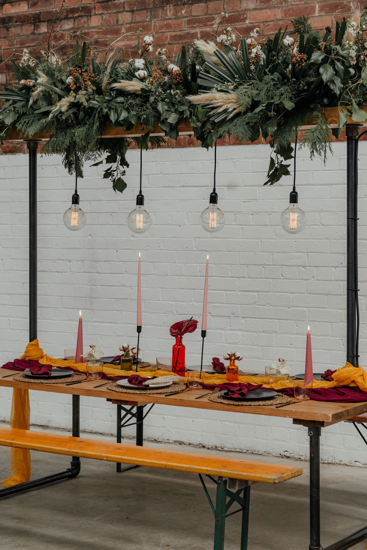 Industrial Meets Boho Wedding Inspiration: Bench seating tables cape with pendant lights and wedding florals