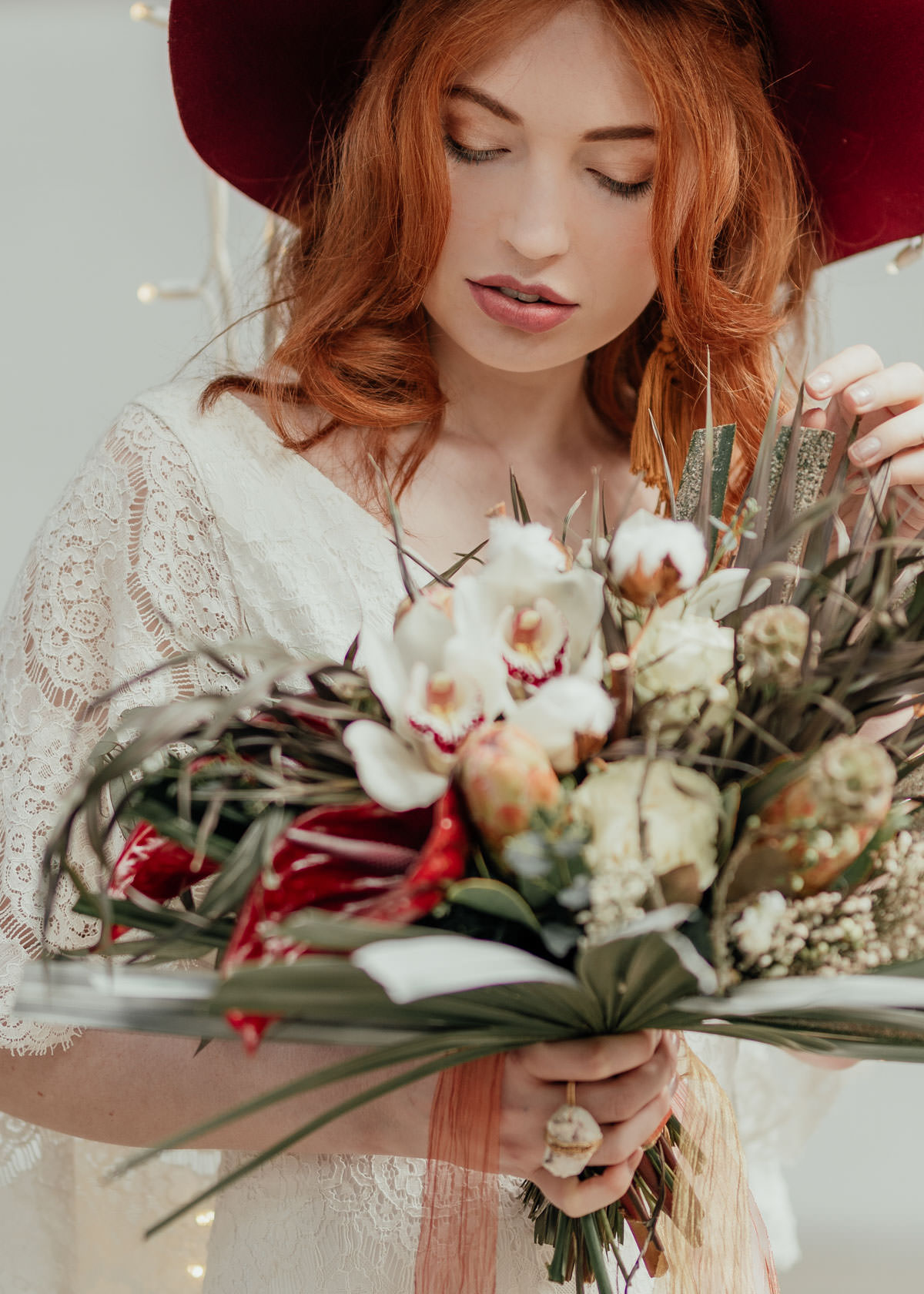 Industrial Meets Boho Wedding Inspiration: Red head bride wearing hat and holding wedding bouquet