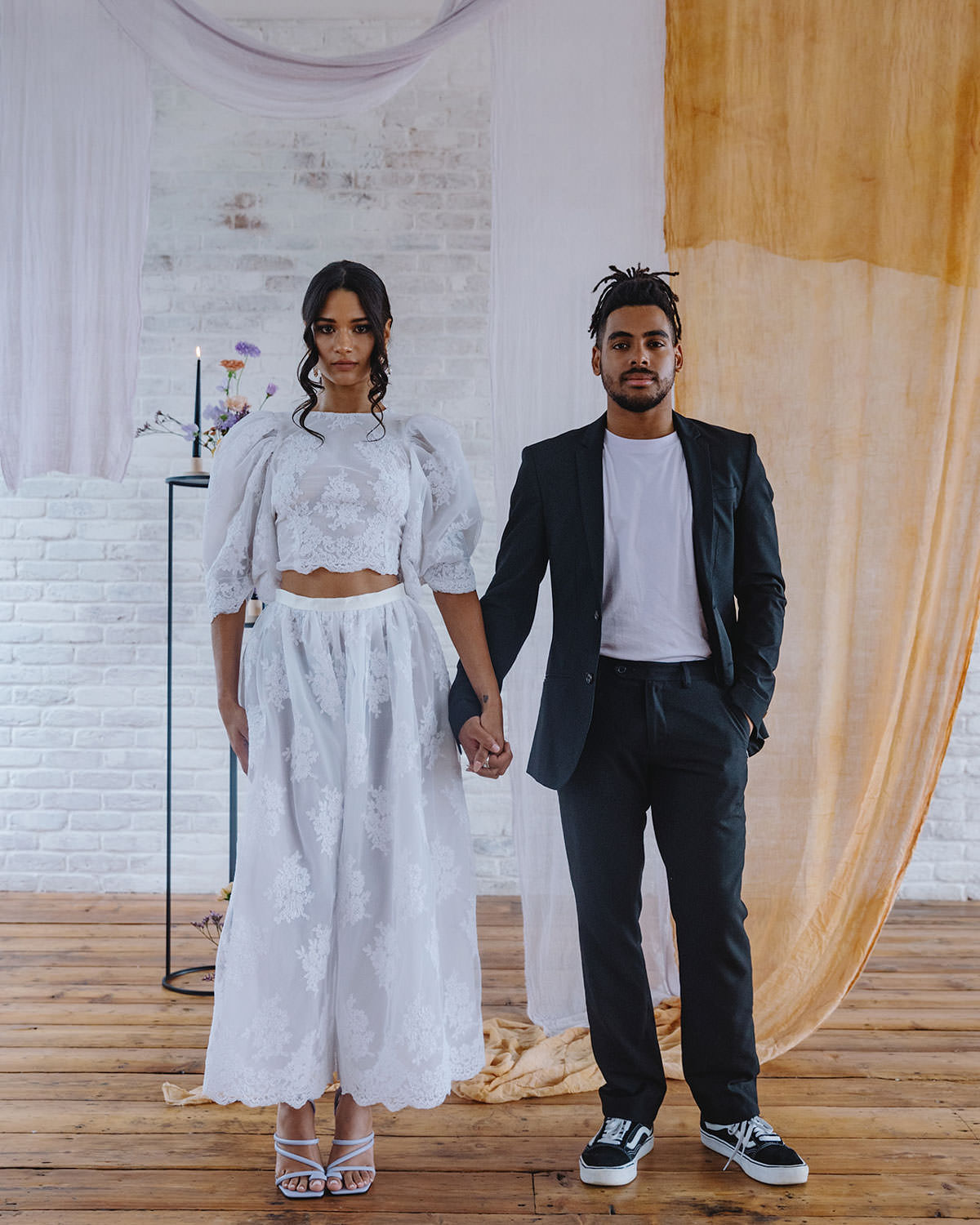 modern bridal styling with an Industrial , loft style backdrop. A couple hold hands. The bride is wearing a lace Velvet Johnston dress and the groom is wearing a white tee and tailored blackout.